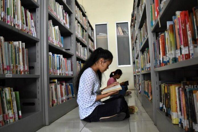 Memanfaatkan waktu dengan membaca buku di perpustakaan.