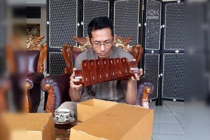 Sastrawan Lampung Arman Az sedang memegang gamolan pekhing atau cetik